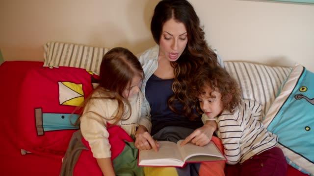 mor en bok till hennes två barn i sängen - cosy pillows mother child bildbanksvideor och videomaterial från bakom kulisserna