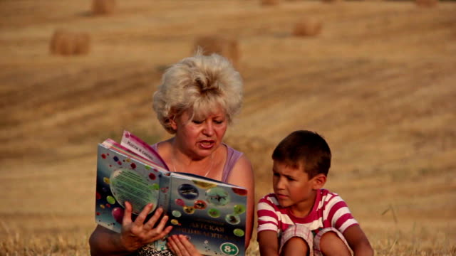 mother reading a book to son, in the field, woman reading a book to boy video