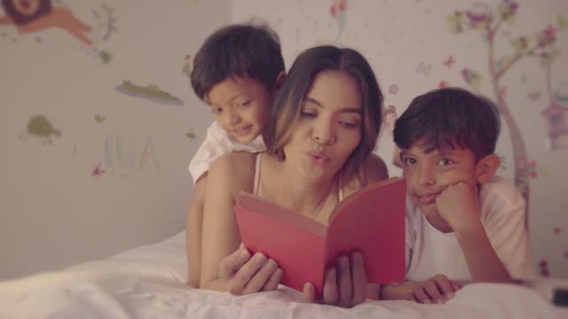 eine mutter liest eine geschichte für seine kinder - lateinische schrift stock-videos und b-roll-filmmaterial