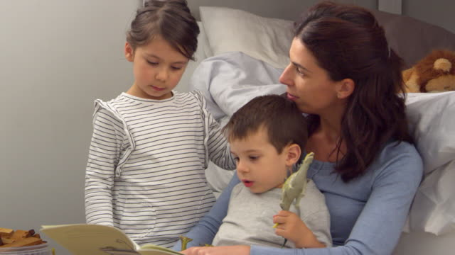 Mother Reading Story To Children In Their Bedroom video