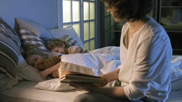Mother Reading to Children Before Sleeping