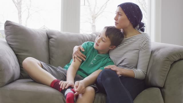 Mother Recovering from Cancer A young mother who is recovering from cancer holds her son as they sit on the couch. The mother is wearing a head scarf cancer patient stock videos & royalty-free footage
