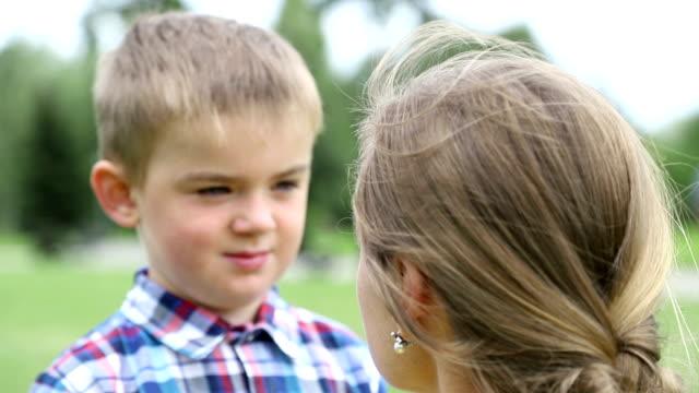 mamma grälar son, barnet är sorgligt, böjde han huvudet ner. närbild, slow motion - parent talking to child bildbanksvideor och videomaterial från bakom kulisserna