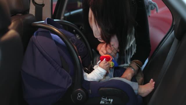 mamma säkra sitt barn i bilbarnstolen på bilen - människorygg bildbanksvideor och videomaterial från bakom kulisserna