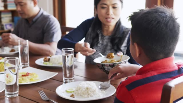 Mother serving food to son at dining table