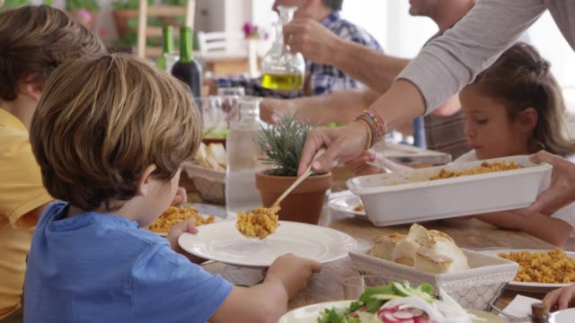 Mother serving pasta to children at dining table