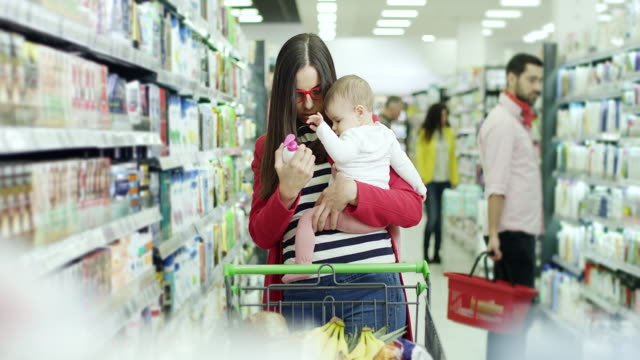 Mother shopping with daughter in grocery store or supermarket video