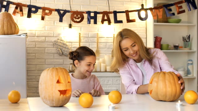 mother showing carved jack-o-lantern to daughter and suddenly scaring her, fun - zucca video stock e b–roll