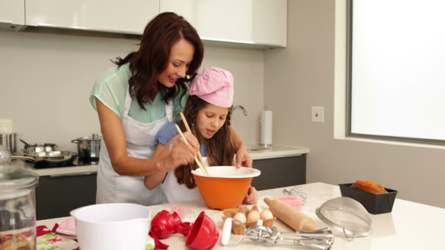 Mother showing her daughter how to bake video
