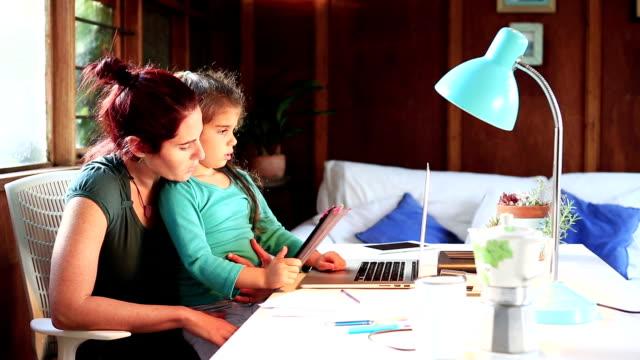 Mère est assise à la maison de bureau avec fille sur ses genoux - Vidéo