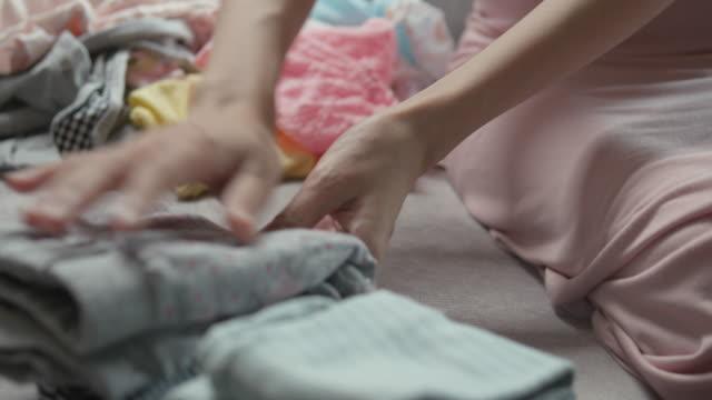 vídeos de stock, filmes e b-roll de matriz que senta-se no sofá e que dobra a roupa do bebê - pilha arranjo