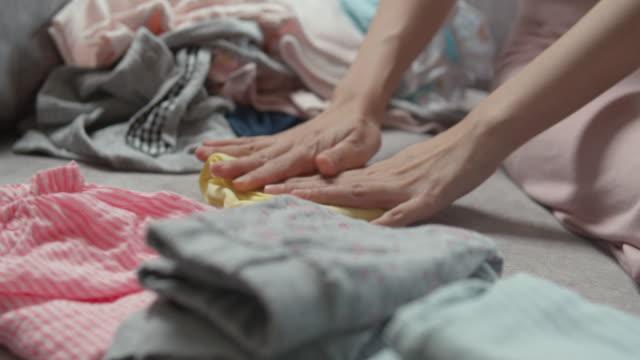mother sitting on sofa and folding the baby clothes - pranie filmów i materiałów b-roll