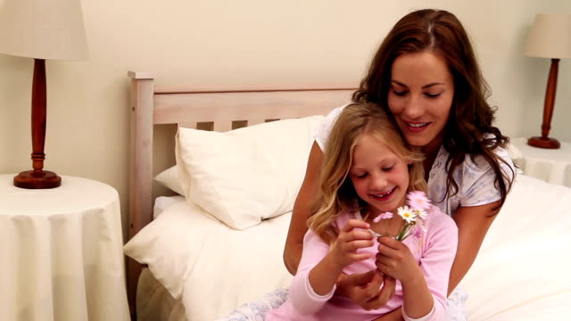 Mother sitting with her little girl holding flowers video