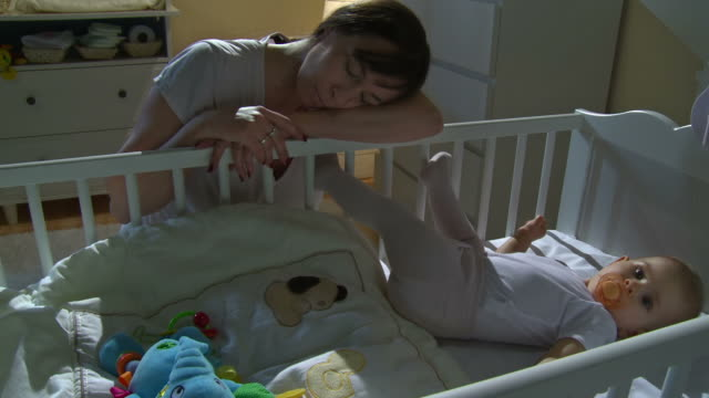 HD CRANE: Mother Sleeping Beside Sleepless Baby video