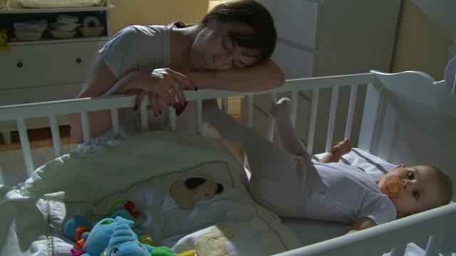 stockvideo's en b-roll-footage met hd crane: mother sleeping beside sleepless baby - background baby