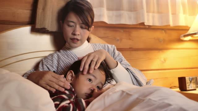 母は息子を寄り添う。病気の日に家にいる - 悩む点の映像素材/bロール