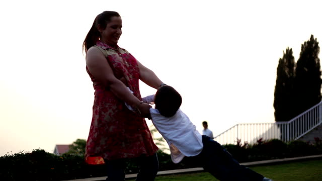 Mother spinning her son in the nature video