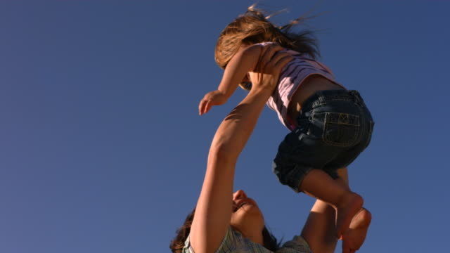 Mother spinning young daughter in sky video