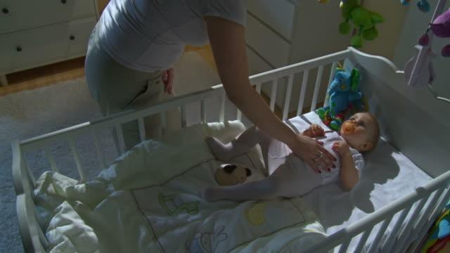 stockvideo's en b-roll-footage met hd crane: mother stroking her sleepless baby - background baby