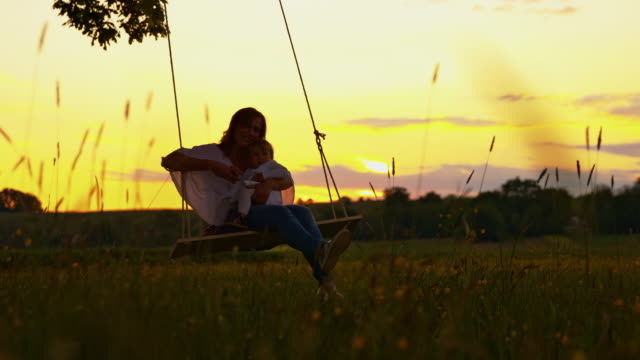 SLO MO Mother swinging with her baby girl at sunset video