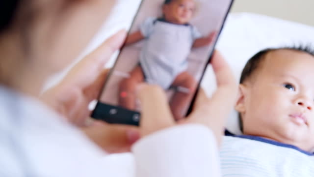 vídeos de stock e filmes b-roll de mother taking a picture of her cute little baby boy - fotografar