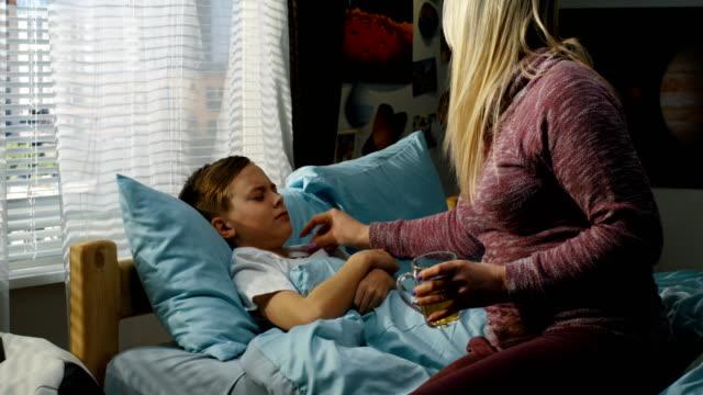 vídeos de stock e filmes b-roll de mother taking care of sick son - doença