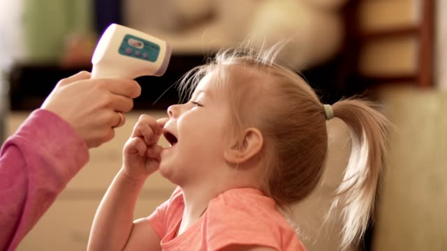 Mother taking daughter's temperature using a digital thermometer indoors in 4k video