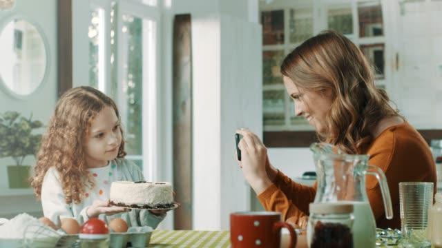 mor som tar bilder av hennes dotter med tårta - birthday celebration looking at phone children bildbanksvideor och videomaterial från bakom kulisserna