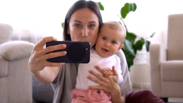 Mother taking selfie with adorable baby girl