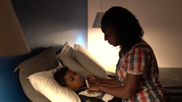 Mother taking son's temperature at home video