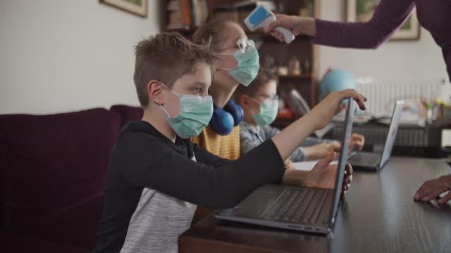 vídeos de stock, filmes e b-roll de mãe tirando a temperatura das crianças frequentando a aula online da escola. - salas de aula