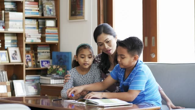 Mother talking to kids while assisting in homework Mother assisting son in homework while sitting with girl on sofa. Smiling family is talking while studying at table. They are wearing casuals at home. guidance stock videos & royalty-free footage