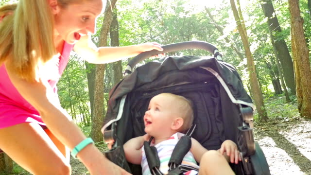Mother talking to toddler daughter as she pushes her in stroller at park video