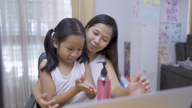 Mother teaches daughter to wash hands with alcohol gel, to wash hands with alcohol gel - vídeo