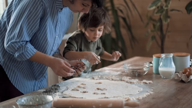 Mother Teaches Little Boy How to Make Gingerbread Cookies Hardworking Blond Boy Preparing Gingerbread Cookies In Kitchen With His Mom cookie cutter stock videos & royalty-free footage