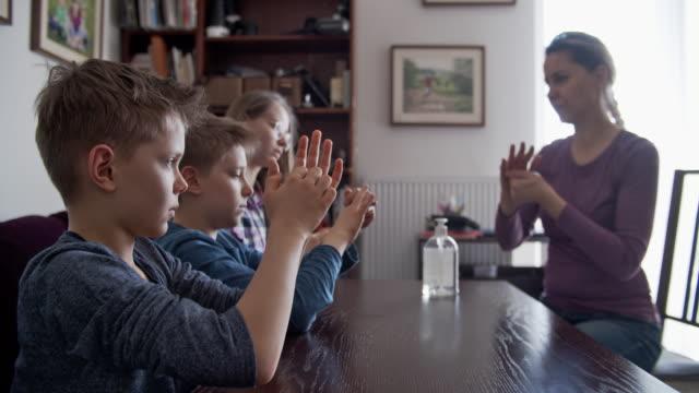 vídeos y material grabado en eventos de stock de madre enseñando a los niños a desinfectar las manos con gel de manos antibacteriano - brote