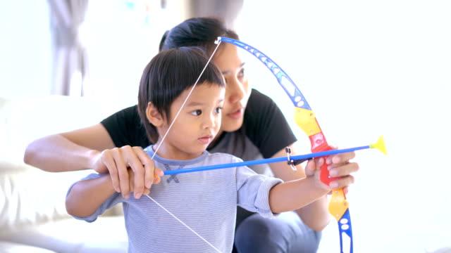 vidéos et rushes de mère fils mignon au tir à l'arc d'enseignement. - tir à l'arc