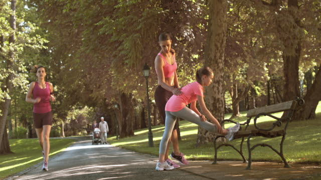 DS Mother teaching daughter stretching exercises in the park Wide dolly shot of a mother teaching her daughter how to stretch on a park bench. tank top stock videos & royalty-free footage