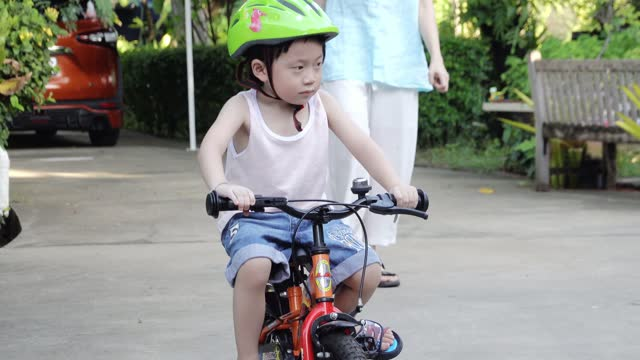 Mother teaching little boy ride bicycle