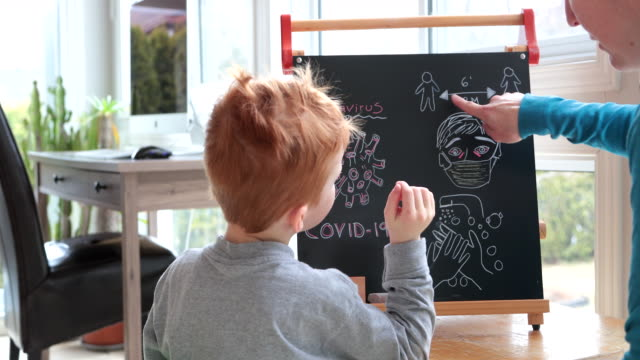 mother teaching redhead son about coronavirus and covid-19 - didattica a distanza video stock e b–roll