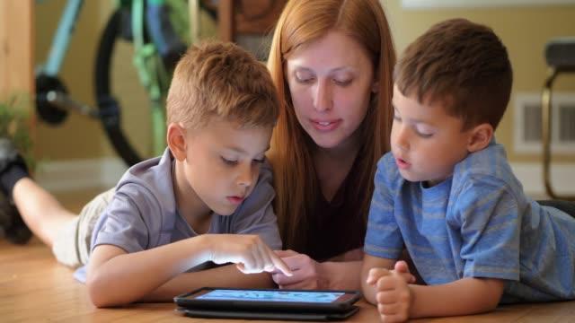 Mother teaching sons using digital tablet.