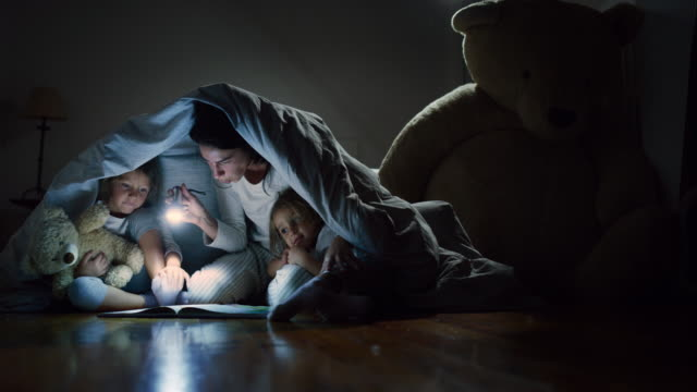 A mother tells stories to her daughters in the dark illuminating with a torch under the blanket.