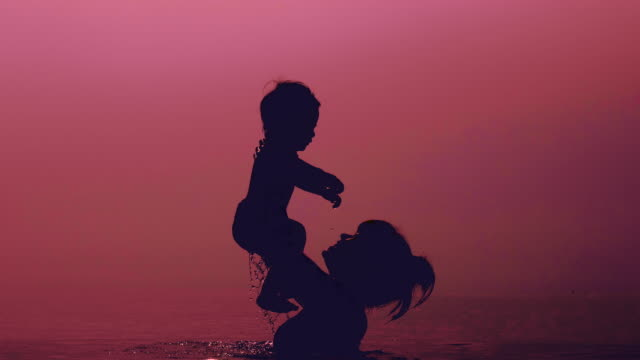 vídeos de stock e filmes b-roll de mother throwing son in sea at sunset - brinquedos na piscina