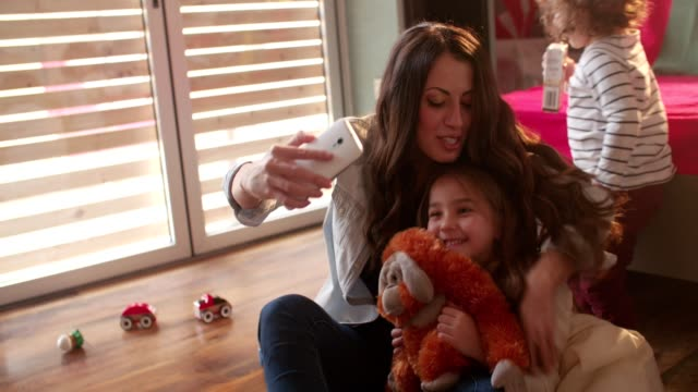 Mother tickling her daughter and taking a selfie with her video