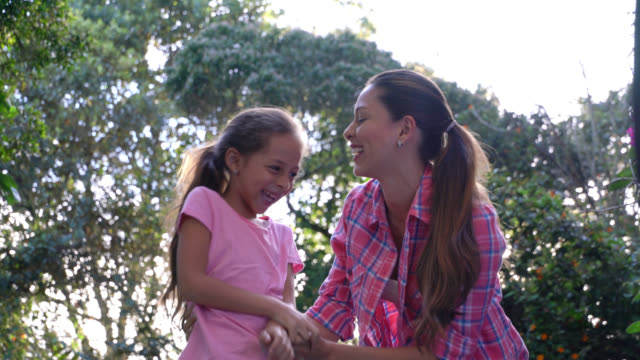 mother tickling her daughter looking very happy and laughing - fare il solletico video stock e b–roll