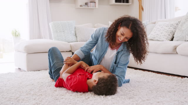 Mother Tickling Son As They Play Game In Lounge Together Mother tickling son lying on lounge rug at home - shot in slow motion wrestling stock videos & royalty-free footage