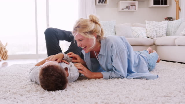 mother tickling son as they play game in lounge together - fare il solletico video stock e b–roll