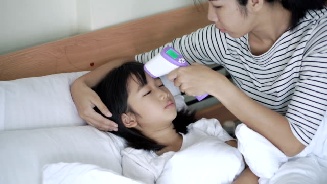 Mother touching daughter forehead measuring temperature, taking care, health.4k