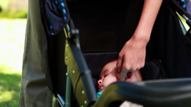 vídeos de stock e filmes b-roll de mãe tocando seu bebé numa pram dormir - dormitar