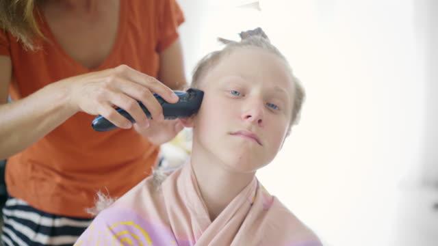 mutter trimmt die langen haare eines sohnes tun einen jungen neuen stil haarschnitt mit elektrischen haarschneider. gemeinsames familien- und erziehungskonzept. - friseur lockdown stock-videos und b-roll-filmmaterial